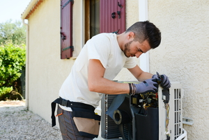 man working on an outdoor central air conditioning unit
