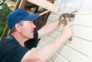 A handyman working with white siding on a house.