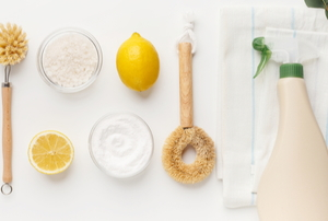 natural cleaning products like lemon and baking soda with spray bottle and scrub brush