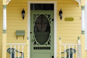 porch of yellow house with mint green front door