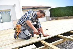 A handyman constructing a wood deck and using an impact driver.