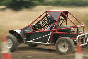 A dune buggy driving on a dirt track.