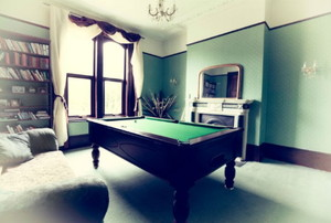 Pool table in a room with green walls and dark wood
