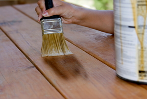 Use a paintbrush to stain a wooden deck.
