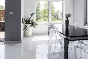 clear plastic chairs in sleek, modern dining room with white floor and black table