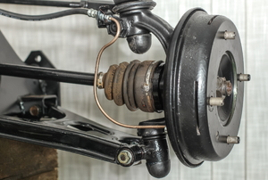Front suspension members of an older car with new brake drum exposed with spindle, ball joints and steering rack visible