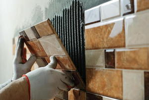 Someone applying tile to wall.