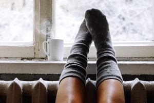 feet with socks on a radiator next to a winter window and hot drink