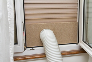 A portable air conditioning unit is set up with the hose venting out a window.
