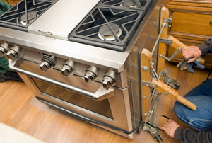 Worker Removes Appliance Dolly from New Kitchen Range