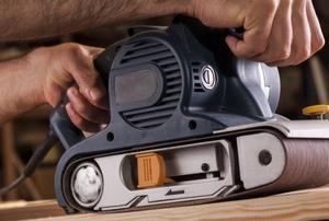 hands using belt sander on wood