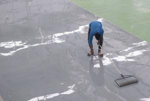 Man rolling epoxy on a floor