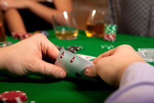 A player showing a hand with a pair of aces in a poker game.