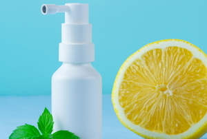 spray bottle with cut lemon and sprig of mint