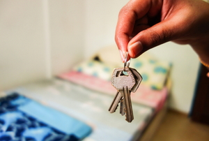 A set of house keys in the foreground with a bedroom in blurry focus in the background.