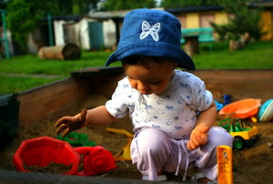A baby playing in a sandbox.