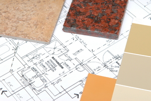 A collection of paint chips and granite samples over a home's blueprint.