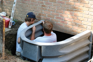 Two men install egress window wells.