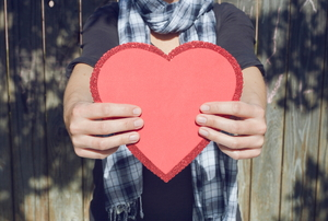 A woman holding a red paper heart.