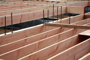 Wooden floor joists and rebar laid out for a wood foundation.