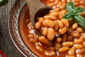 bowl of cooked beans with basil, hot pepper and wooden spoon