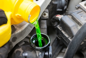 pouring green coolant in a car radiator
