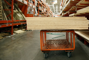 A stack of wood on an orange cart in a home improvement store.