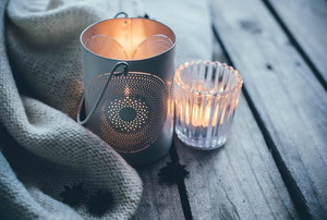 A couple of candles and a blanket on a wood table.