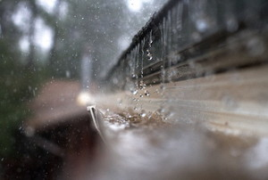 Heavy rain falls into a rain gutter.