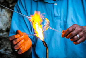 hands holding glass over a flame to form it into a curved wand shape
