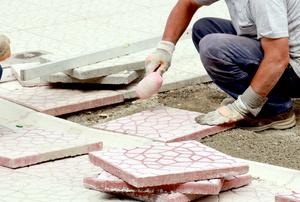 A man installs driveway pavers.