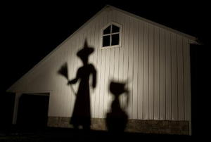 Creepy shadows projected onto the side of a house.