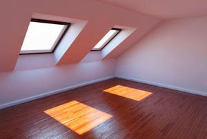 Attic windows casting squares of light on a finished floor.