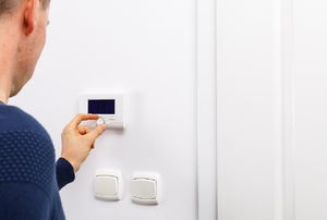 A man adjusting a thermostat on a white wall.
