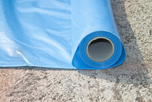 A roll of blue plastic sheeting used for a crawlspace vapor barrier.