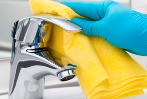 cleaning bathroom faucet with gloves and sponge