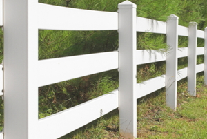 vinyl fence running between grass and bushes
