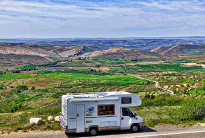 an RV on the road with green landscape in the distance
