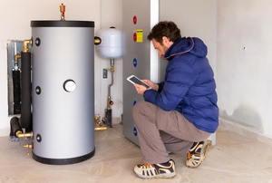 Man kneeling near a water heater