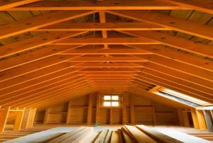 Looking down an unfinished attic toward a single window.