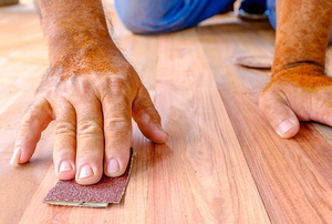 hands sanding wood flooring