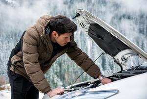 A man in a coat checking under the hood of a car in a winter setting.