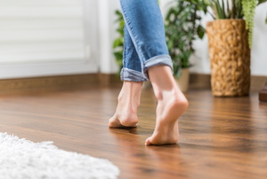 Bare feet walking on a hardwood floor.