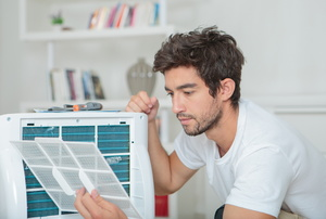 A man sets up a room AC unit.