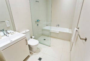 A bathroom with frameless shower door.
