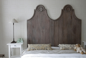 A rustic style headboard sits behind a bed.