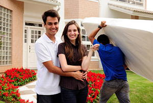 Real estate: couple moving house, mover carries mattress