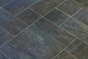 Dark, slate tile flooring laid in various size pieces.