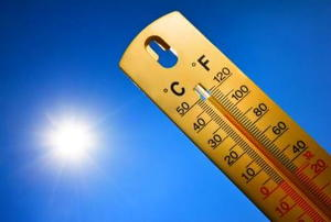 A thermometer against a blue sky with sun in background.