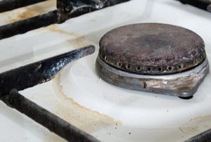 rusty gas stovetop with spilled water